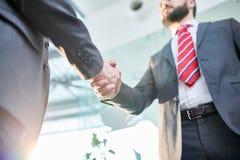 Bearded Entrepreneur Greeting Business Partner. Low angle view of bearded entrepreneur wearing classical suit greeting his business partner with handshake while royalty free stock photos