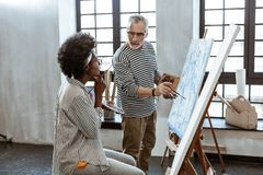 Bearded experienced artist giving piece of advice to his student. Piece of advice. Bearded experienced artist wearing glasses giving piece of advice to his royalty free stock image