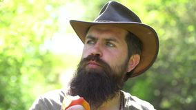 Bearded farmer with shovel. Close up portrait of man farmer having fun and eating apple in a farm. Country life. Hipster. Farmer relaxing at nature background stock video footage