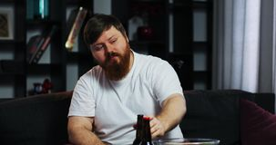 Bearded fat man drinks bear and watches TV with remote control in his hand, sitting at the table with pop-corn.  stock footage