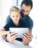 Bearded father with his young son using tablet PC in sunny room.Dad and little boy playing together on mobile computer, resting in Stock Image
