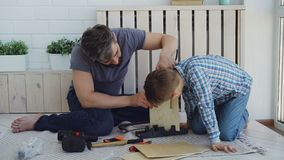Bearded father and little cute son making birdhouse of wooden sheets at home. Childhood and parenthood concept doing. Bearded father and little cute son making stock footage