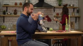 Bearded father playing with baby little son, sitting at the table while his wife cooking dinner lunch food. Happy. Bearded father playing with his baby little stock footage