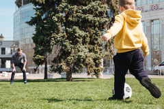 Bearded father playing football with his little son. Picture of bearded father playing football with his little son outdoors in the park. Looking aside Stock Images