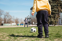 Bearded father playing football with his little son. Picture of bearded father playing football with his little son outdoors in the park. Looking aside stock photo