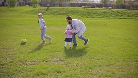 Bearded father plays at the stadium in football with two daughters. Summer day, green grass. Bearded father plays at the stadium in football with two daughters stock video
