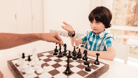 Bearded Father and Son Playing Chess on Table. Happy Family Concept. Board on Table. Young Boy in Shirt. Indoor Joy. Board Games Concept. Modern Hobby Concept royalty free stock images