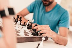 Bearded Father and Son Playing Chess on Table. Happy Family Concept. Board on Table. Young Boy in Shirt. Indoor Joy. Board Games Concept. Modern Hobby Concept royalty free stock photo