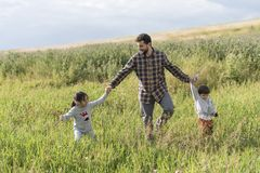 Bearded father walking with her daughter and son in spring day Royalty Free Stock Photography