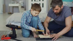 Bearded father and young cute son making birdhouse of wooden sheets at home. Childhood and parenthood concept. Bearded father and young cute son making birdhouse stock video