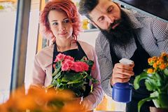 Bearded flower seller and a redhead female watering flower bouqu. Ets royalty free stock image
