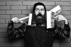 Bearded foreman holding various building tools with satisfied face. Bearded foreman, long beard, brutal caucasian hipster with moustache in uniform holding stock photography