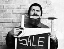 Bearded foreman holding various building tools with serious face. Bearded foreman, long beard, brutal caucasian hipster, moustache in uniform holding various stock photography