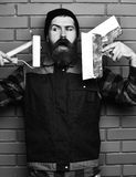 Bearded foreman holding various building tools with satisfied face. Bearded foreman, long beard, brutal caucasian hipster with moustache in uniform holding royalty free stock photography