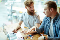 Bearded Friends Chatting in Coffeehouse Stock Images