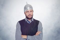 Bearded funny man in a cap of aluminum foil. Concept art phobias stock photo