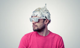 Bearded funny man in a cap of aluminum foil Royalty Free Stock Image