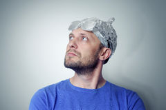 Bearded funny man in a cap of aluminum foil. Concept art phobias Royalty Free Stock Images