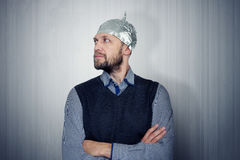 Bearded funny man in a cap of aluminum foil. Concept art phobias Royalty Free Stock Photos
