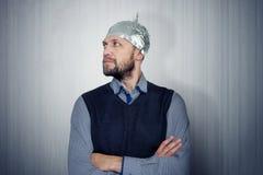 Bearded funny man in a cap of aluminum foil. Concept art phobias Royalty Free Stock Photos