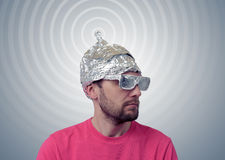 Bearded funny man in a cap of aluminum foil sends signals Stock Photo