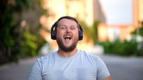 Bearded funny man puts on their clothes, turns on music, listens to energetic music, dances. Close-up royalty free stock images