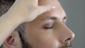 Bearded gay or metrosexual man getting makeup. Closeup portrait of attractive bearded metrosexual or gay man with eyes closed getting makeup of eyelid with brush stock video