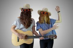 Bearded girls with sunglasses and hat playing guitar and dancing royalty free stock photo