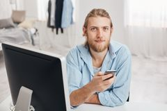 Bearded good-looking male office worker with gentle smile reads notification on smart phone, sits in front of screen at. Coworking space with cell phone, sends Stock Photos