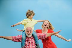 Bearded grandfather and grandson with mother playing with on sunny day. Grandson sits on the shoulders of his royalty free stock image