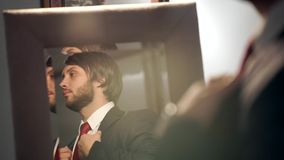 Bearded groom dressing in a beautiful wedding day. The groom wears a red tie in the reflection of a mirror coat stock footage