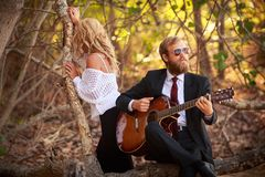 Bearded guitarist and girl sit on tree branch Stock Photos
