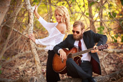 bearded guitarist and girl sit on tree branch Stock Photo