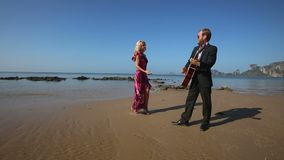 Guitarist stops playing blonde girl in red flirts in low tide stock video footage