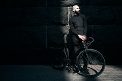 Bearded guy in black clothes with fix bike Royalty Free Stock Image