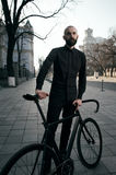 Bearded guy in black clothes stands with fix bike Royalty Free Stock Images