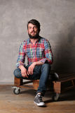 Bearded guy in colorful shirt and jeans sitting with crossed legs. Laminate flooring, serious man, beard and mustache, wooden deck, casual clothes, unshaven Stock Images