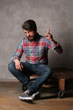 Bearded guy in colorful shirt shows finger up. Laminate flooring, serious man, beard and mustache, wooden deck, casual clothes, unshaven, in studio, red-haired Royalty Free Stock Image