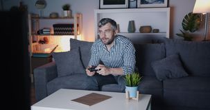 Bearded guy enjoying video game at home at night on sofa holding joystick. Bearded guy is enjoying video game at home at night sitting on sofa holding joystick stock video