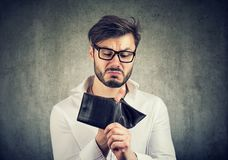 Poor man having no money in wallet. Bearded guy in glasses being broke having holes in wallet instead of money royalty free stock photography