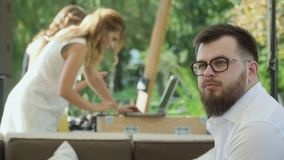 Bearded guy in glasses observes after girl using laptop on blurred background stock footage