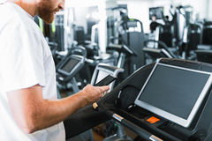 Bearded guy in gym at treadmill Royalty Free Stock Photography