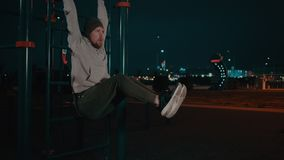 Bearded guy is hanging on training area in park in night and lifting legs. Athletic man is training in sportive area in city park at night. He is holding hands stock video footage