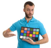Bearded guy holds a Color and grayscale control table Royalty Free Stock Photos