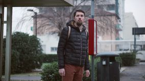 Bearded guy in jacket stands on public bus stop stock video