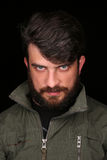 Bearded guy in khaki jacket looking into the camera. Close.up. Black Royalty Free Stock Images