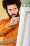 Bearded guy painting a picture in his studio Stock Images