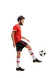 Bearded guy in a red jersey juggling a football Stock Photo