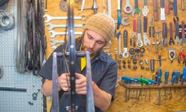 Bearded guy repairing bicycle in the workshop stock images