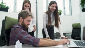 A bearded guy and two young girls are discussing the work plan in the office in the workplace. The senior manager shows stock video